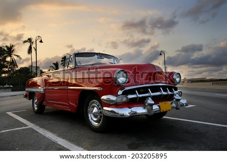 HAVANA, CUBA - NOVEMBER 3, 2009: View of red classic vintage american car parked, commonly used as private taxi in Havana, Cuba. - stock photo