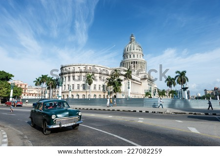 HAVANA, CUBA - OCTOBER 8, 2014: Old classic American green car rides in front of the Capitol. Before a new law issued on October 2011, Cubans could only trade cars that were on the road before 1959.  - stock photo