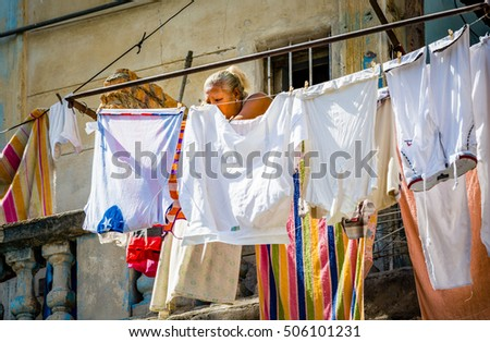 HAVANA, CUBA - OCTOBER 29, 2015 Woman tends to laundry hanging in the Cuban sunshine in Havana, Cuba in October 2015