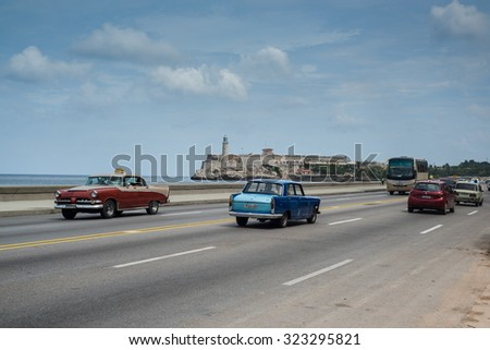 Havana, Cuba - September 28, 2015: Classic american car drive  on Malecon sea front promenade in Havana,Cuba. Classic American cars are typical landmark and tourist attraction for whole Cuban island.