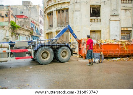 HAVANA, CUBA - SEPTEMBER 4, 2015: Waste collection vehicle picking up garbage container from the streets