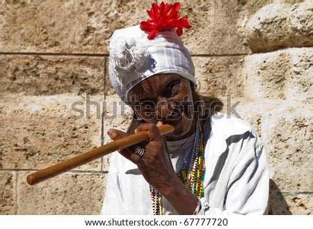 HAVANA-DECEMBER 24:Wrinkled old lady with a huge cigar wearing typical clothes and afrocuban religious necklaces December 24, 2010 in Havana.
