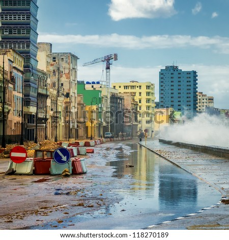Havana during a hurricane with big waves crashing against the seaside wall and debris on the street - stock photo