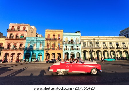 HAVANA - FEB 5: Classic red Car in  Old Havana main street, on February 5th, 2015 Havana, Cuba.Old cars and the UNESCO protected part of Old City are attracting millions of tourists every year - stock photo