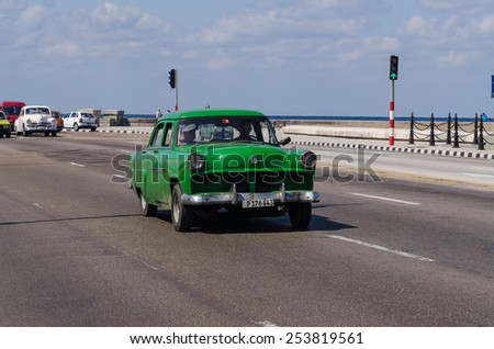 HAVANA - FEB 13: Vintage cars driving on Malecon boulevard, one of  the main thoroughfares in Havana on February 13, 2015 - stock photo
