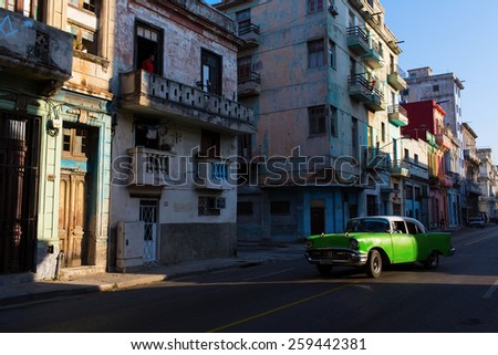 HAVANA - FEBRUARY 17: Classic car and antique buildings on February 17, 2015 in Havana. These vintage cars are an iconic sight of the island - stock photo