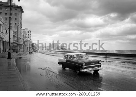 HAVANA - FEBRUARY 19: Classic car and antique buildings on February 15, 2015 in Havana. These vintage cars are an iconic sight of the island - stock photo