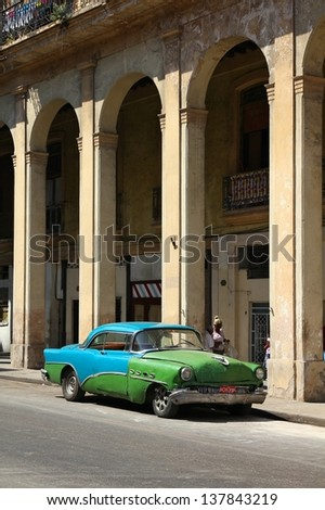 HAVANA - FEBRUARY 27: People walk past old car on February 27, 2011 in Havana, Cuba. Recent change in law allows the Cubans to trade cars again. Most cars in Cuba are very old because of the old law. - stock photo