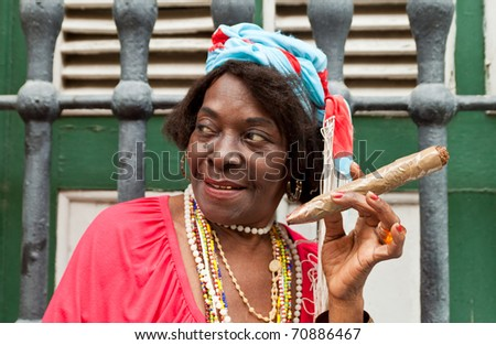 HAVANA-FEBRUARY 10:Wrinkled old lady with a huge cigar wears typical clothes and afrocuban religious necklaces February 10,2011 in Havana. - stock photo