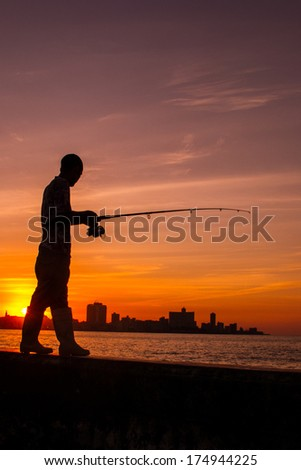 havana fishermen at sunset with skyline - stock photo
