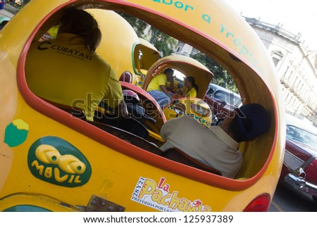 HAVANA - JANUARY 11: Cuban coco taxis on the street January 11, 2013 in Havana. The yellow taxi cabs can fit  a maximum 2 passengers. - stock photo