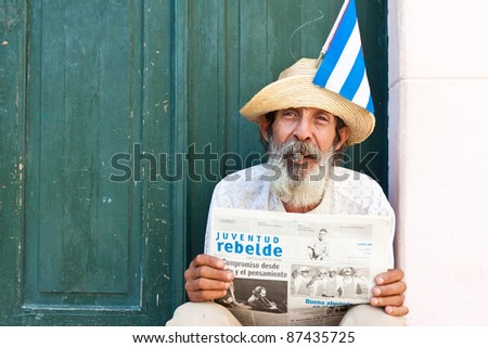 HAVANA - OCT 20: An old man with a cigar and a newspaper on Oct 20,2011 in Havana. With the growth of foreign tourism some people make their living posing as traditional Cuban characters. - stock photo