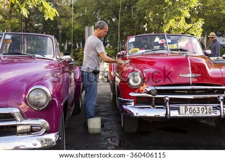 HAVANA,-OCTOBER 14: Man washing old car on streets of Havana in October 14, 2015 in Havana. With 2.4 mil. inhabitants in the city and 3.7 in its urban area,Havana is the largest city in the Caribbean
