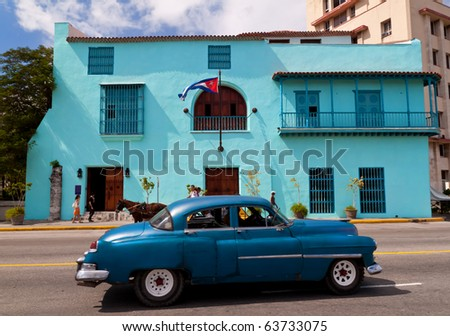 HAVANA - OCTOBER 23: Old  car in front of a building with the cuban flag October 23, 2010 in Havana. A tourist attraction by themselves, a  large number of vintage cars are still in use in Cuba. - stock photo