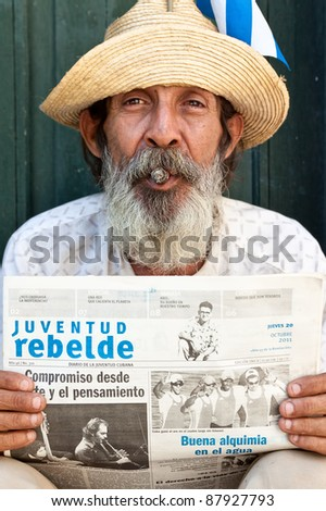 HAVANA-OCTOBER 20:Old man with cigar and newspaper October 20,2011 in Havana.With the growth of foreign tourism some people,working for tips,make their living posing as traditional cuban characters - stock photo