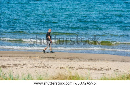 Havang, Sweden - May 18, 2017: Documentary of everyday life at Havang nature reserve. Tattooed male person taking a walk along the beach holding a plastic bottle.