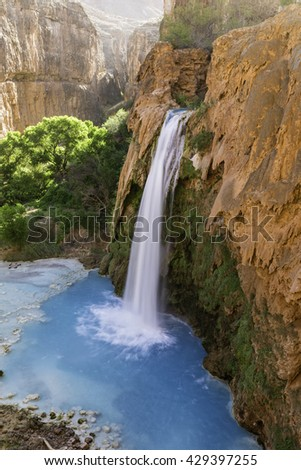 Havasu Falls plunges into a deep blue-green pool, with Cataract Canyon behind lit by the morning sun, on Havasupai Indian Reservation in the Grand Canyon. - stock photo