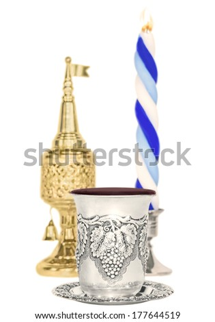 Havdalah set,selective focus on silver kiddush wine cup.Jewish religious ritual after end of Sabbath.Braided lit candle.Gold color spice container,traditional tower shape with bell, flag.Vertical view - stock photo
