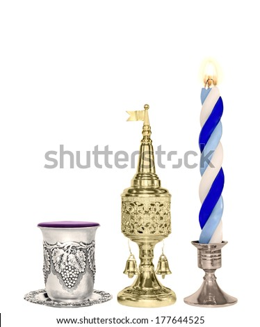 Havdalah set.Silver kiddush wine cup,gold color spice box,braided lit candle.Jewish religious ritual after end of Sabbath.Spice container,traditional tower shape,bell and flag.Vertical view.  - stock photo