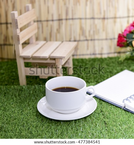 Have a cup of black coffee.Writing on copy space note book . with Pencil on green grass Background.With selective focus.