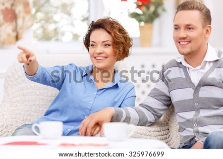 Have a look. Overjoyed upbeat young couple sitting in the armchairs and drinking tea while expressing gladness - stock photo