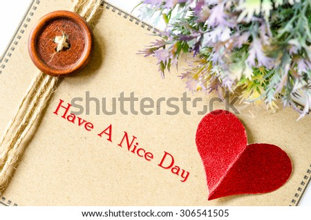 Have a nice day on brown heart and red paper with leaf on whtie background. - stock photo