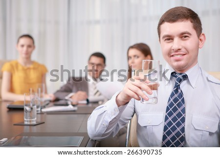 Have a sip of water. Young smiling manager wearing shirt and tie holding a glass of water at the business meeting with his team sitting on the background - stock photo