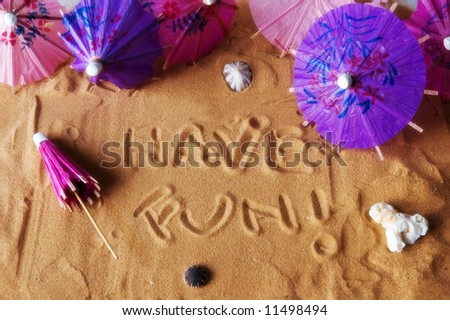 Have fun! written on sand with colorful umbrellas and seashells. Soft focus for dreamy atmosphere.