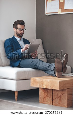 Have some work to do. Handsome young man keeping legs on table and working with touchpad while sitting on the couch in office - stock photo