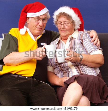 Having a coffee at christmas elderly couple - stock photo