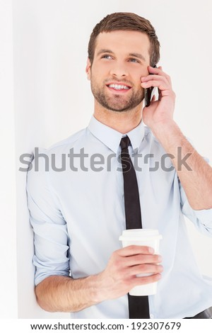 Having a coffee break. Cheerful young man in shirt and tie talking on the mobile phone and drinking coffee while leaning at the wall - stock photo