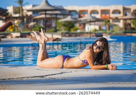 Having a good time on the poolside. Side view of attractive young women in bikini posing on the poolside - stock photo