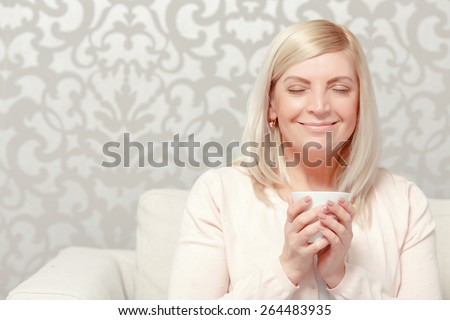 Having a rest at home. Beautiful mature woman reads a magazine copyspace relaxing on the couch at home - stock photo