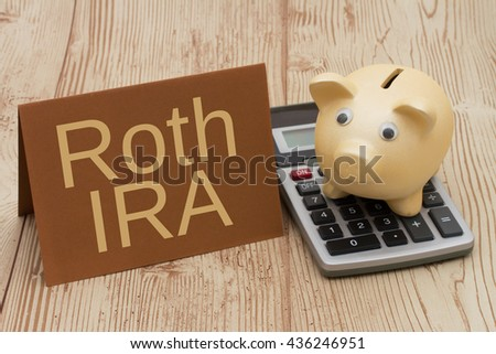 Having a Roth IRA plan, A golden piggy bank, card and calculator on wood background with text  Roth IRA - stock photo