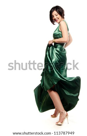 Having fun and smiling with a green dress in a white isolated studio
