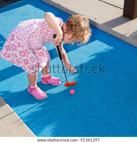 Having fun at miniature golf site on sunny summer afternoon. - stock photo
