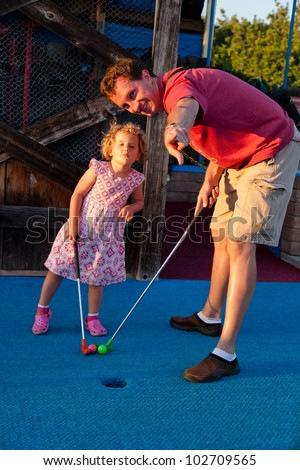Having fun at miniture gold site on sunny summer afternoon. - stock photo