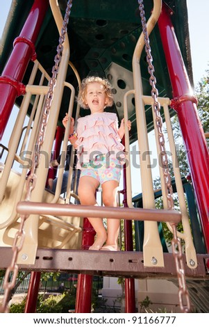 Having fun at playground in the park on Saturday morning. - stock photo