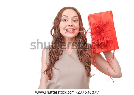 Having fun. Funny pretty red-haired woman standing against isolated white background holding stripe of big red present in her mouth. - stock photo