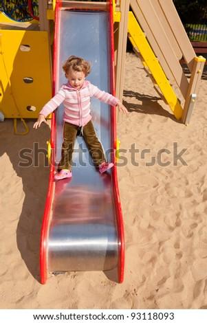 Having fun playing on playground on sunny morning. - stock photo