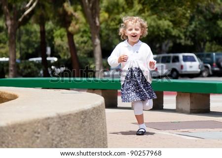 Having fun running around the fountain in the park. - stock photo