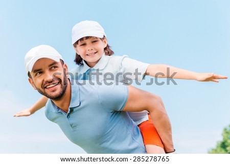 Having fun together. Cheerful young man carrying his son on shoulders while standing outdoors - stock photo