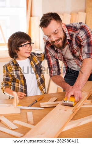 Having fun while working together. Smiling young male carpenter showing his son how to sand wood in his workshop  - stock photo