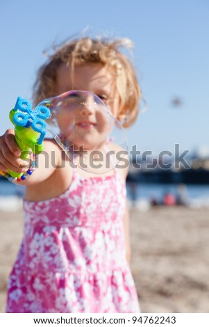 Having fun with bubbles  on a beach on sunny day. - stock photo