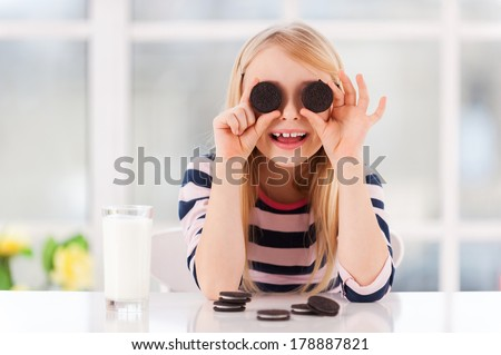 Having fun with cookies. Cheerful little girl covering eyes with cookies while sitting at the table with glass of milk on it  - stock photo