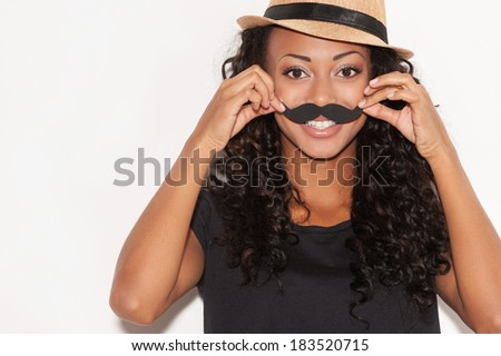 Having fun with face mustache. Cheerful young African woman in funky hat holding fake mustache on her face and looking at camera while standing against white background - stock photo