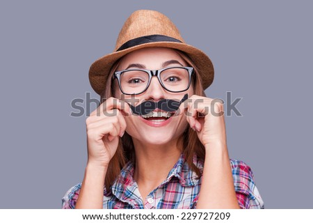 Having fun with face mustache. Cheerful young woman in funky hat holding fake mustache on her face and looking at camera while standing against grey background - stock photo