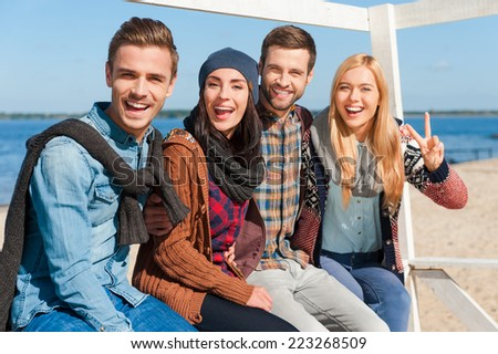 Having fun with friends. Group of young happy people bonding to each other and smiling while sitting at the riverbank - stock photo