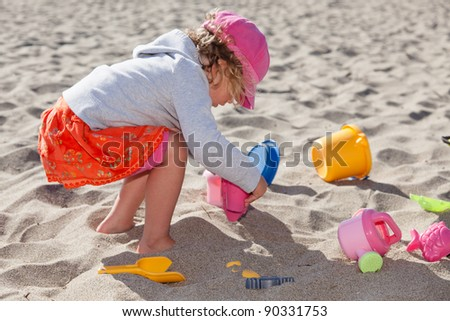 Having fun with sand on the beach in summer. - stock photo