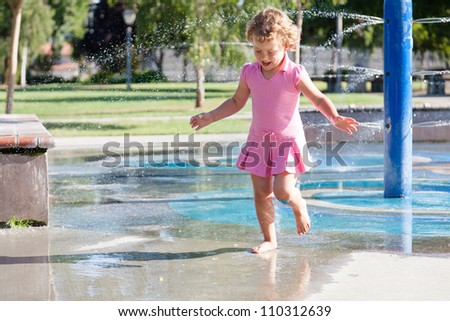 Having fun with water at the playground in park - stock photo
